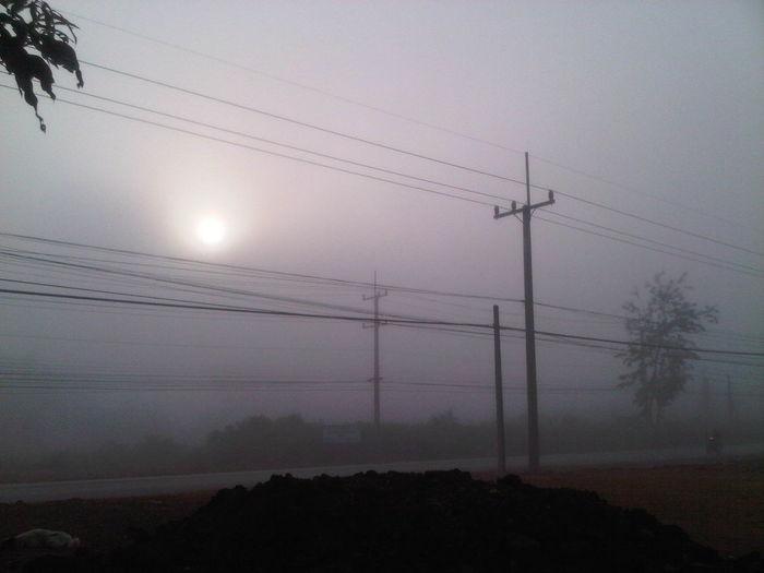 Electricity pylon against cloudy sky