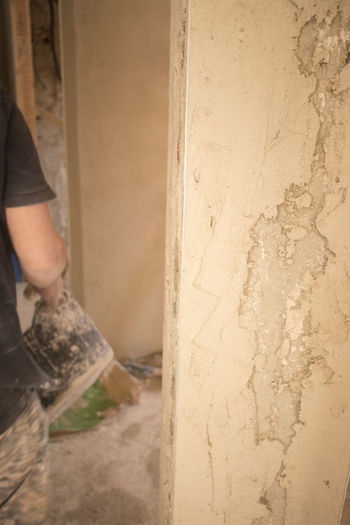 Low section of man working on concrete wall