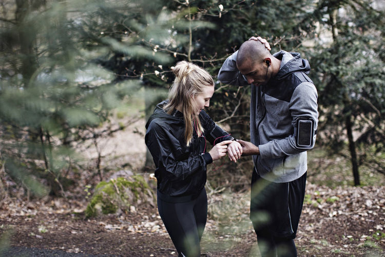 Man and woman standing by tree in forest