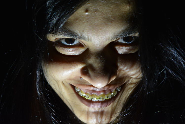 Portrait of smiling young woman in dark
