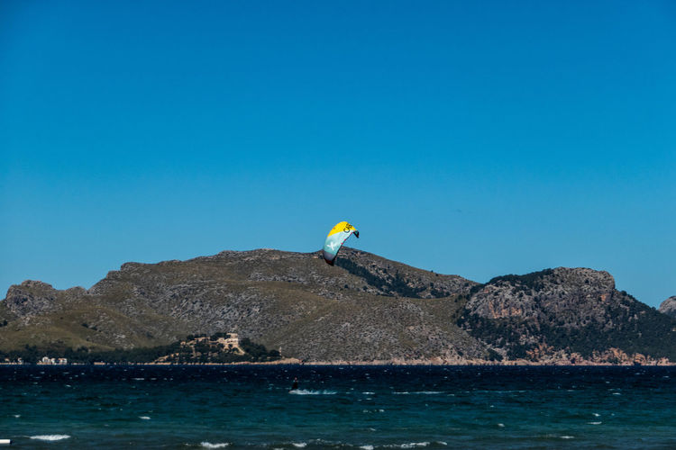 Scenic view of sea against clear blue sky with kite surfer in foreground