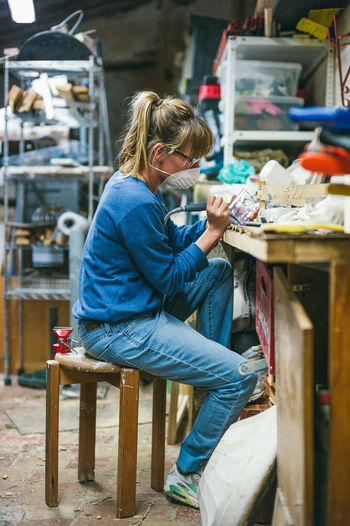 Side view of woman working on glass at workbench in workshop