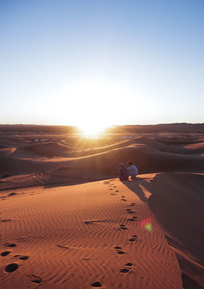 Scenic view of desert against clear sky during sunset