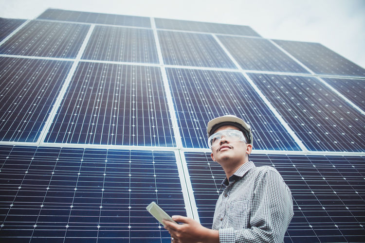 Low angle view of male engineer standing against solar panels