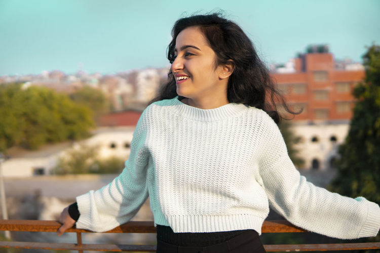 Smiling young woman sitting on looking away