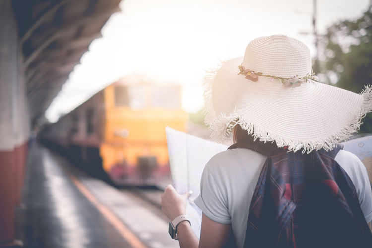 Rear view of woman holding map while standing at railroad station platform in city