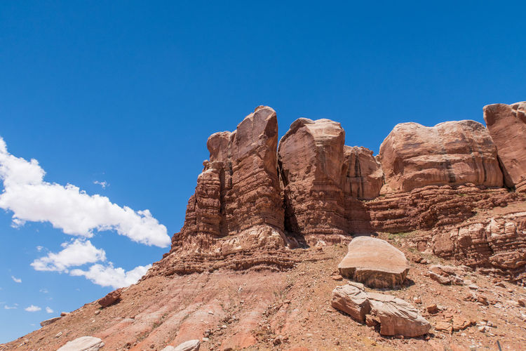 Low angle landscape of massive red boulders forming a wall in bluff, utah