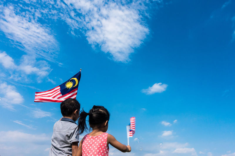 Unknown kids waving Malaysia Flag. Independence day and Merdeka Celebration. Blue sky and copy space. Celebration Children EyeEm Best Shots EyeEm Selects Jalur Gemilang Kids Kuala Lumpur Patriotic Patriotism Adult Blue Blue Sky Boy Cloud - Sky Day Flag Girl Independence Day Leisure Activity Low Angle View Malaysia Men Merdeka Outdoors Patriotism People Real People Rear View Sky Togetherness Two People Waving Women Young Adult