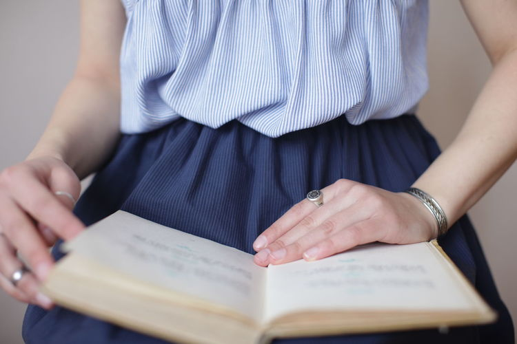 Midsection of girl with book