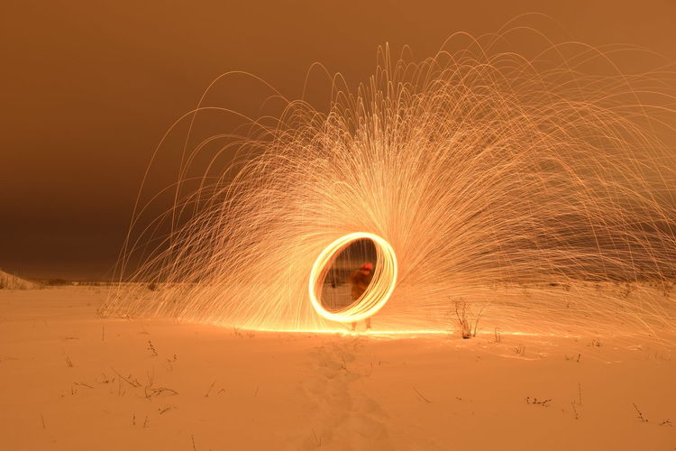 Man Spinning Wire Wool On Field During Winter
