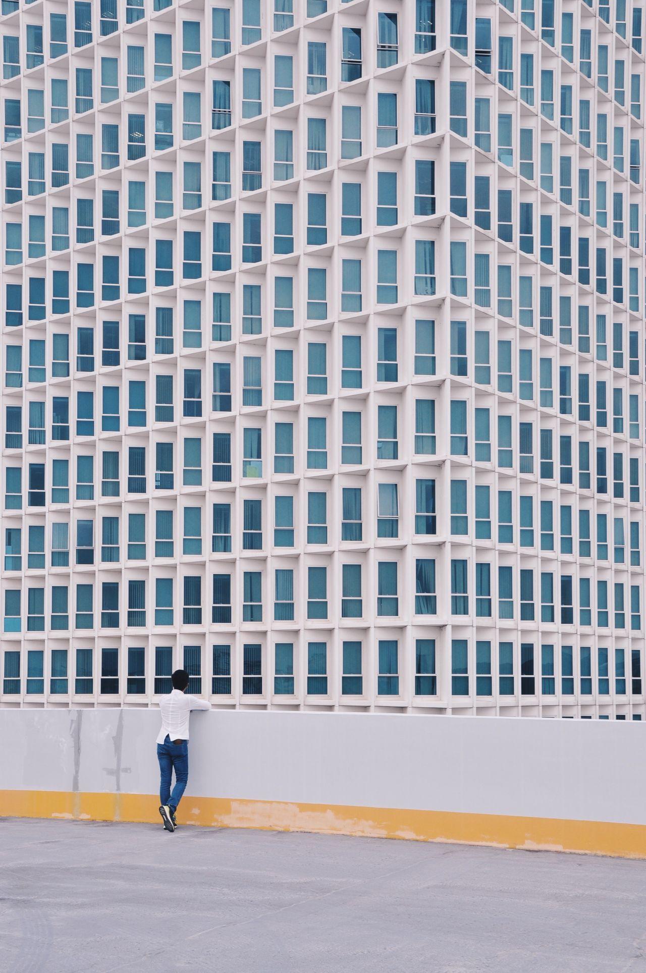 FULL LENGTH OF MAN WALKING ON BUILDING