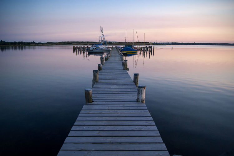 Boats Moored On Pier Over Lake During Sunset