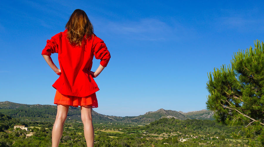 Rear View Of Woman With Hands On Hips Standing Against Blue Sky