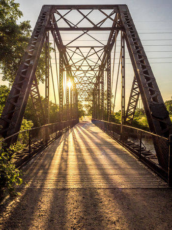 Architecture Bridge - Man Made Structure Built Structure Connection Day Diminishing Perspective Engineering Evening Sun Iron Bridge Metal Nature No People Outdoors Path Shadow Sky Sunbeams Sunlight Sunset Suspension Bridge The Way Forward Transportation Travel Destinations Tree Walking Path