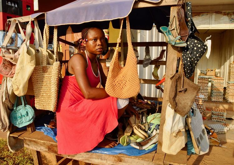 Woman looking away while selling purses in market