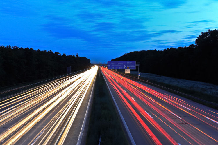 Acceleration Autobahn Blue Hour German Autobahn Highway Illuminated Light Trail Long Exposure Motion Moving Cars Multi Colored Night No People Outdoors Pace Road Sky Speed Time Compression Traffic Transportation Tree