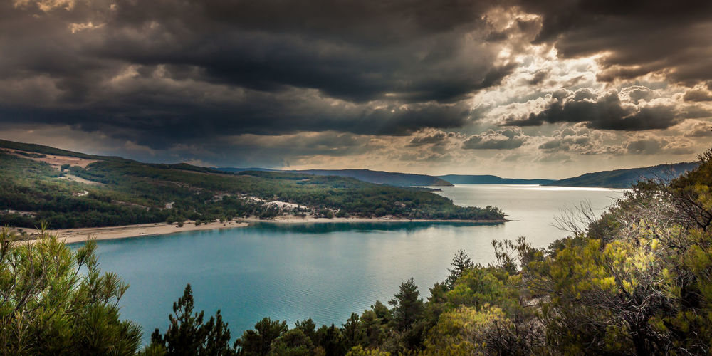 View of calm lake against cloudy sky