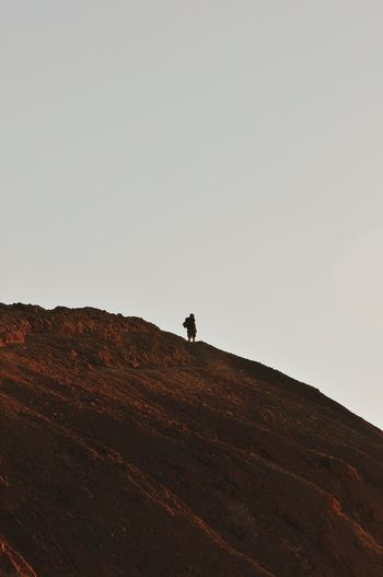 LOW ANGLE VIEW OF PERSON STANDING ON LANDSCAPE