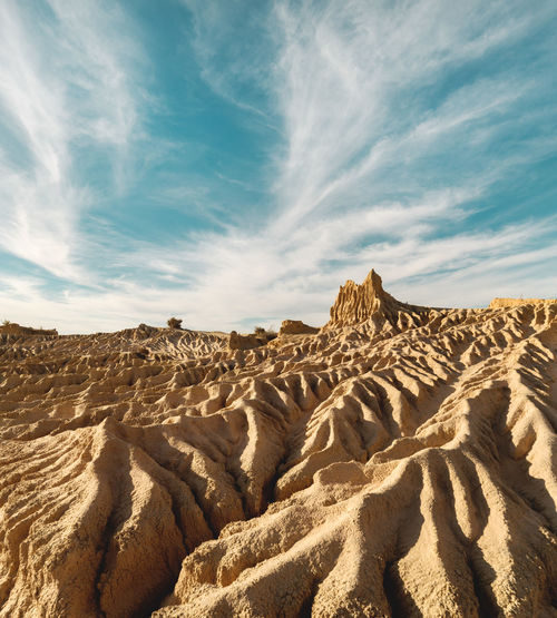 Iconic eroded sand rock formation with dramatic cloud formation in the sky