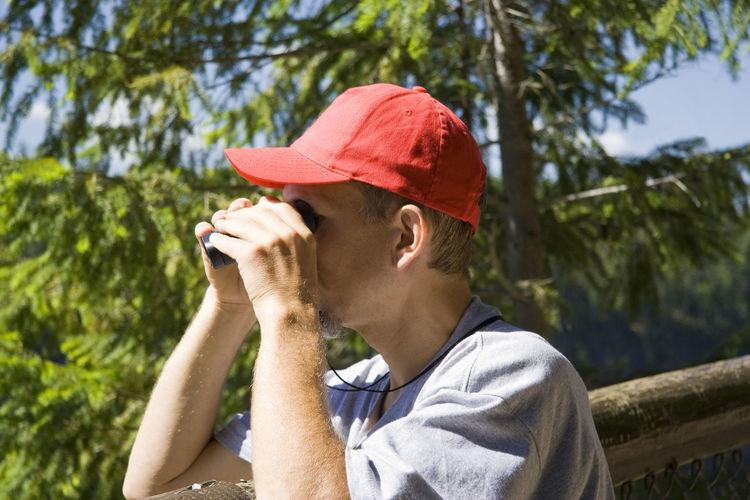 Close-up of man looking through binoculars