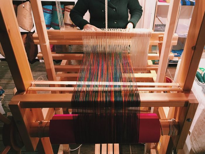 Female worker weaving while using loom in workshop