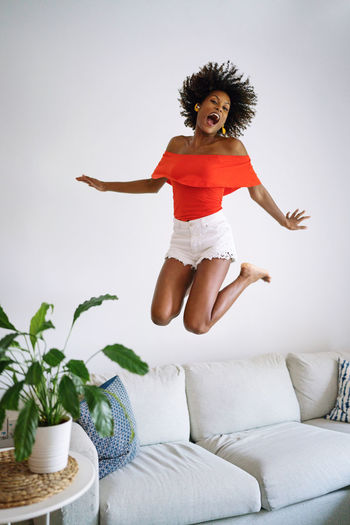 Young woman jumping on sofa at home