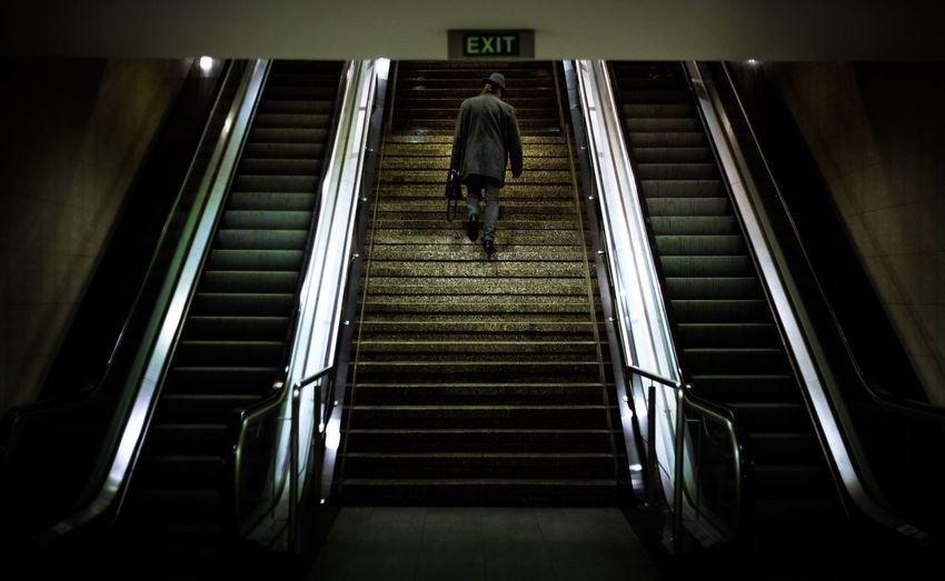 Rear view of man walking on steps by escalator in subway station