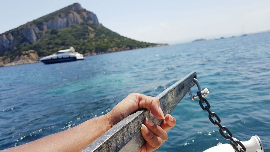 Cropped Hand Of Person Holding Anchor On Boat Over Sea