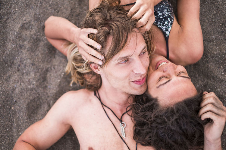 High angle view of young couple lying at beach