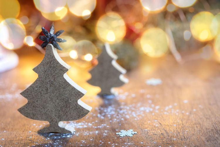Two small wooden Christmas trees with festive light on background, horizontal composition Christmas Christmas Decoration Holiday Celebration Decoration christmas tree Star Shape Shape Christmas Ornament Close-up Christmas Lights Holiday - Event Celebration Event No People Illuminated Tree Event Indoors  Lens Flare