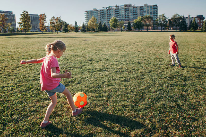 Children playing with ball on grassy land in park