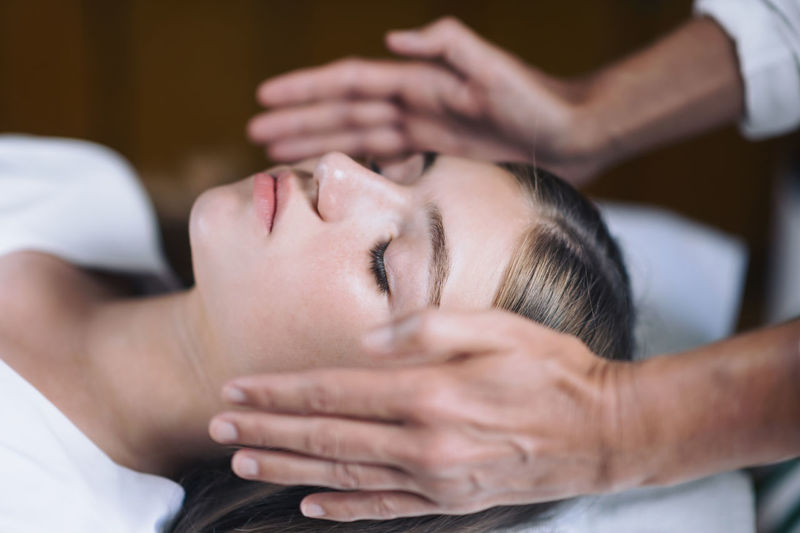Cropped hands of therapist giving reiki treatment to teenage girl on face at spa