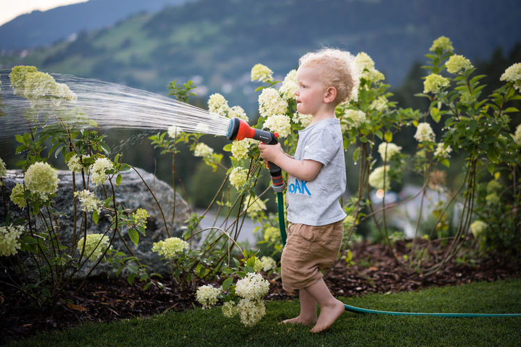 Side view of boy holding plants
