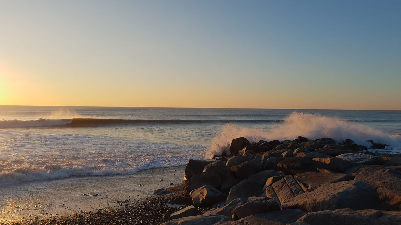 sea, water, sky, beach, horizon over water, horizon, scenics - nature, land, beauty in nature, rock, sunset, motion, solid, nature, tranquility, rock - object, tranquil scene, wave, idyllic, no people, outdoors, rocky coastline, groyne, power in nature