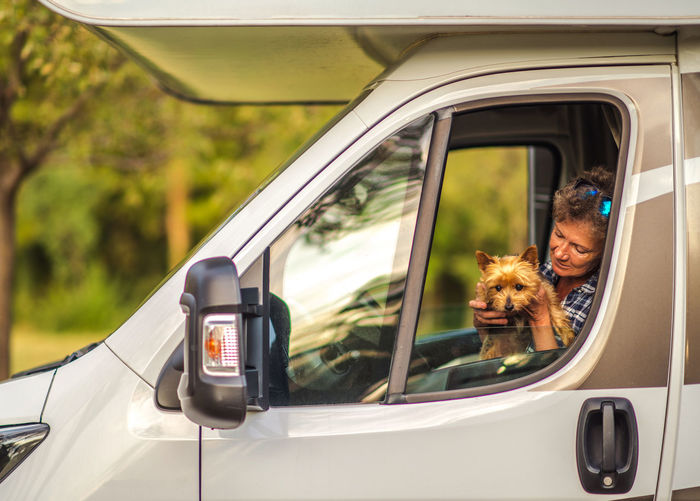 Senior woman with dog sitting in truck