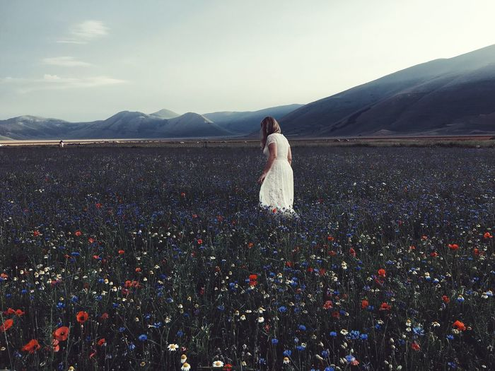 Woman walking amidst flowering plants on field by mountains against sky