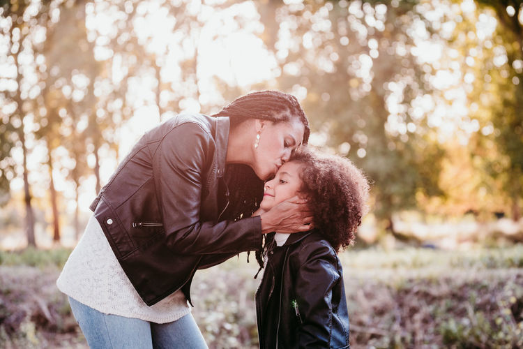 Mother kissing daughter while standing against trees