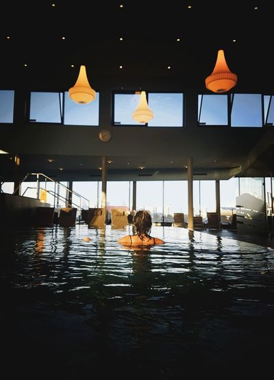 Rear view of man swimming in pool
