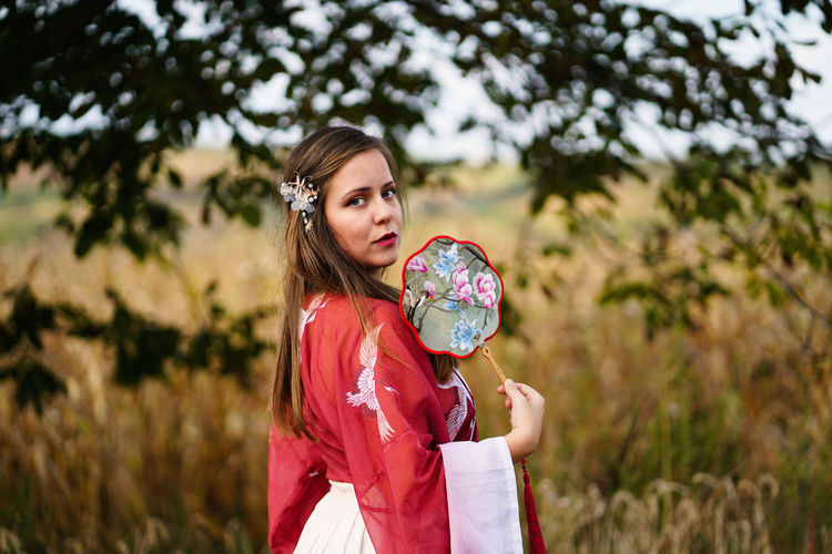 Portrait of woman with hand fan standing on field
