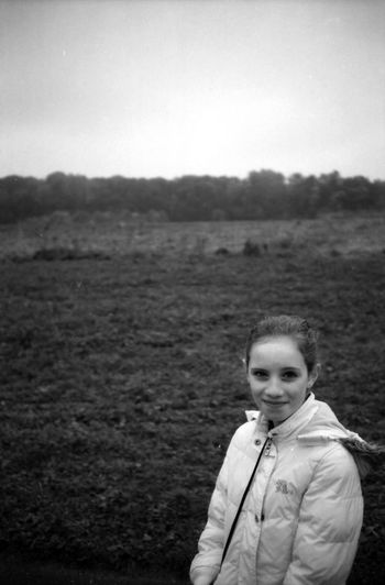Portrait Of Teenage Girl Wearing Warm Clothing While Standing On Grassy Field