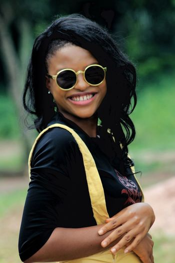 Portrait of smiling young woman wearing sunglasses outdoors