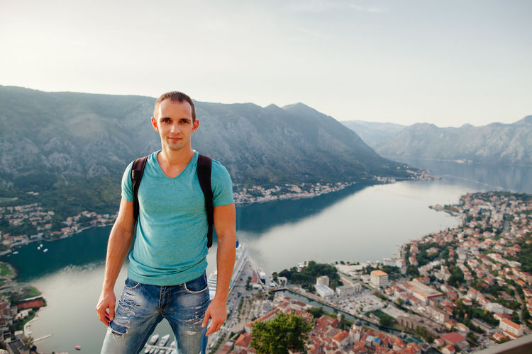 Man travel with backpack in mountains with panorama view. Standing and looking a the camera. Aerial view. EyeEm Best Shots Panorama Travel Adult Adventure Backpack Bay Casual Clothing Cityscape Day Happiness High Angle View Looking At Camera Men Mountain Mountain Range Nature One Man Only One Person Portrait Real People Sky Smiling Standing Young Adult