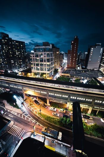 High angle view of illuminated street amidst buildings against sky