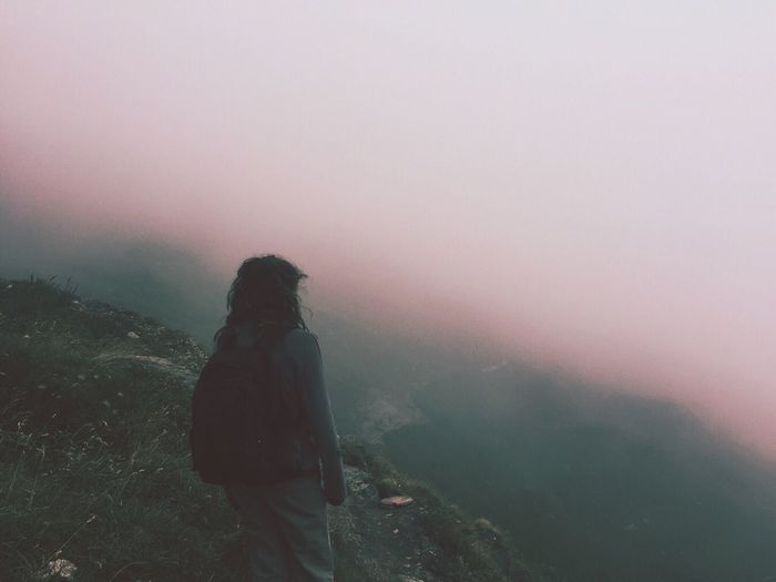 Rear view of woman standing on top of mountain during sunset