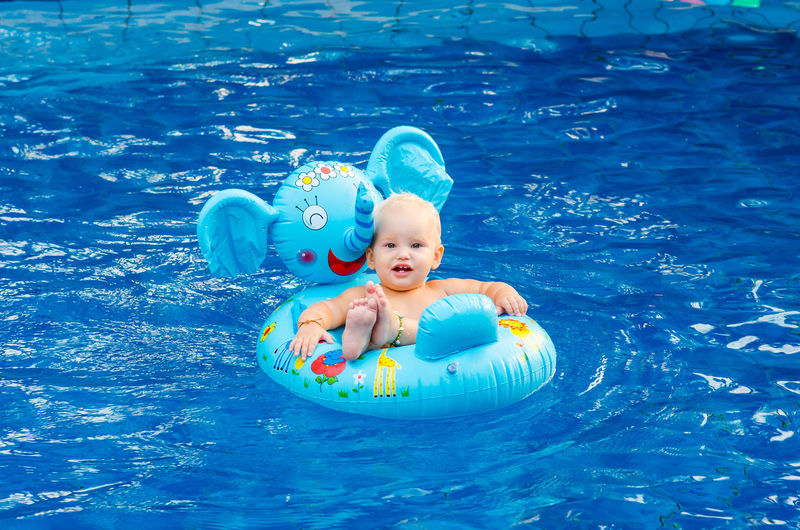 Portrait Of Shirtless Girl Sitting In Inflatable Ring On Swimming Pool