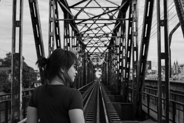 Rear view of woman standing on railway bridge