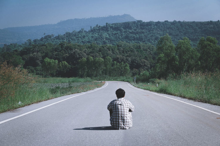 Rear view of man sitting on country road