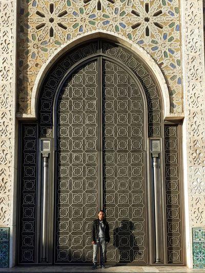Full length of man standing by door of building