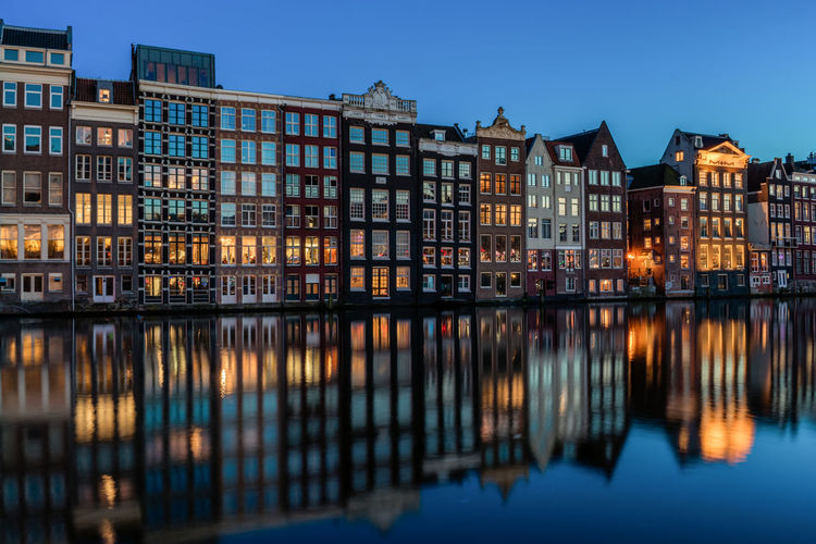 Reflection Of Illuminated Row Houses On Canal At Dusk