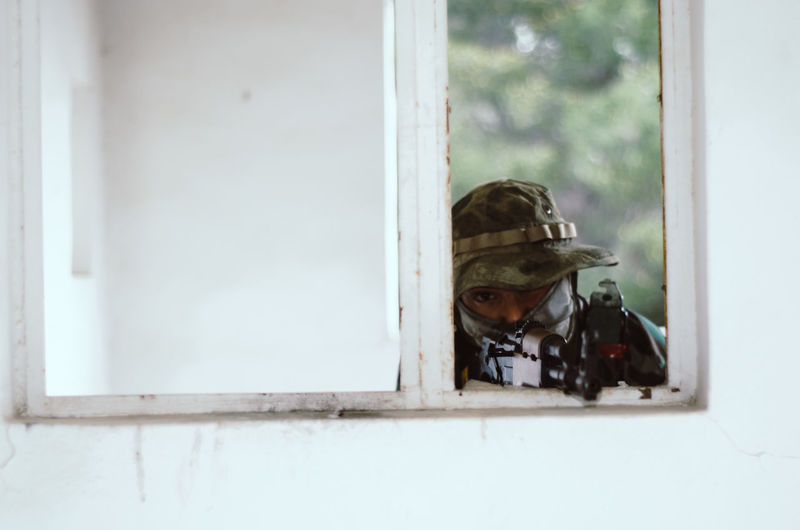 Special forces soldier holding rifle gun aim window white frame cover Reflection Window Day Glass - Material Transparent Helmet One Person Security Portrait Safety Outdoors Protection Headshot Architecture Technology Looking Close-up Digital Camera Airsoft Sniper Trooper Soldier Army Army Soldier Special Forces Aim Aiming Camouflage Clothing Camouflage Hat AK 47 Gun